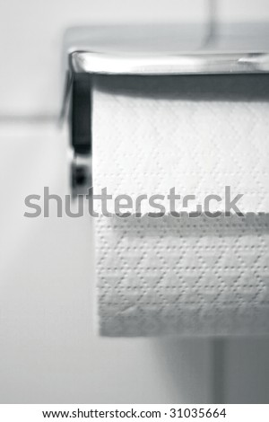 Toilet paper on a holder hanging on the wall