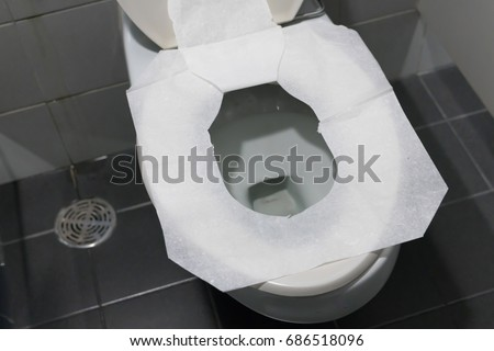 Toilet paper put on Open Toilet seat. Cover The Toilet Seat With Tissue Paper. #686518096