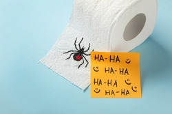 Toilet paper roll with drawn spider and words Ha-Ha  on light blue background. Celebrating April Fool's Day