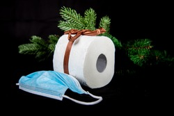 toilet paper roll with loop and a mouth protection mask as christmas present, pine tree brach in the black background