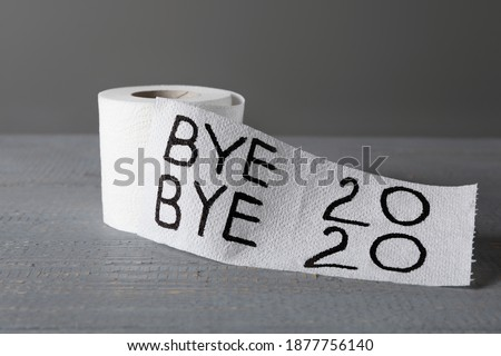 Toilet paper roll with text Bye Bye 2020 on light grey wooden background