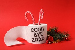 Toilet paper roll with text Goodbye 2020 and Christmas decor on red background