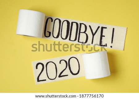 Toilet paper with text Goodbye 2020 on yellow background, flat lay