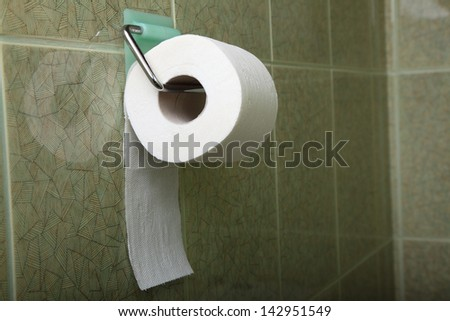 Toilet roll in green toilet, lavatory convenience restroom full tiled wall