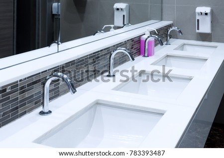 Toilet sink interior of public toilet with of washing hands and mirror