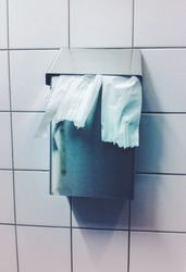 Toilet tissue hanging from a closed metal waste receptable.