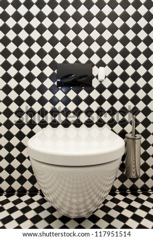 Toilet with a checkered pattern wall, closeup