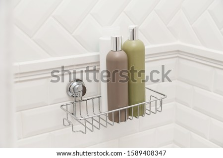 Toiletries bottles on suction cups compact bath shelf, fixing on tiled wall without drilling Foto stock ©