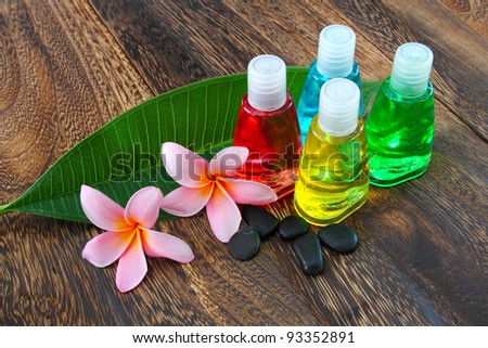 Toiletries with stones and plumeria flower on wooden floor.