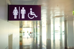 Toilets icon. Public restroom signs with a disabled access symbol. Interior of airport terminal.