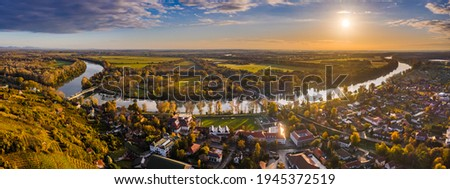 Tokaj, Hungary - Aerial panoramic view of the town of Tokaj wine region with town of Tokaj with River Tisza and golden sunrise at background on a warm autumn morning