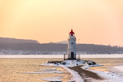 Tokarevsky lighthouse at the tip of the Egersheld peninsula in Vladivostok on an early winter morning at dawn among the ice.