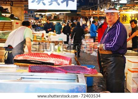 TOKYO - APRIL 4 : Fish seller with tuna cut at Tsukiji Market, the biggest wholesale market in Japan April 4, 2007 in Tokyo, Japan.