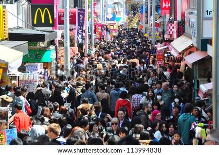 TOKYO - APRIL 1 2012: People, mostly youngsters, walk through Takeshita Dori near Harajuku train station on Sunday April 1 2012. Takeshita Dori is considered a birthplace of Japan's fashion trends. - stock photo