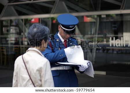 TOKYO - AUGUST 13: Japanese policeman explains directions to an elderly lady in central  on August 13, 2010 in Tokyo.
