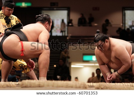 TOKYO - JANUARY 18: Two sumo wrestlers in their starting positions for a fight in the Tokyo Grand Sumo Tournament January 18, 2010 in Tokyo, Japan.