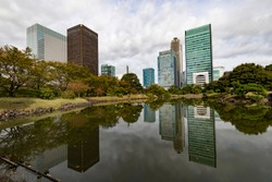 Tokyo, Japan, buildings reflected in a pond in Kyu Shiba Rikyu garden, on a cloudy day