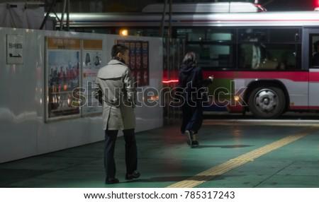 TOKYO, JAPAN - DECEMBER 30TH, 2017. Pedestrian walking in the street of Shibuya at night