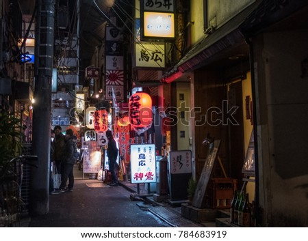 TOKYO, JAPAN - DECEMBER 30TH, 2017. People walking in a narrow back alley in Shimbashi neighborhood full of small colorful restaurants.