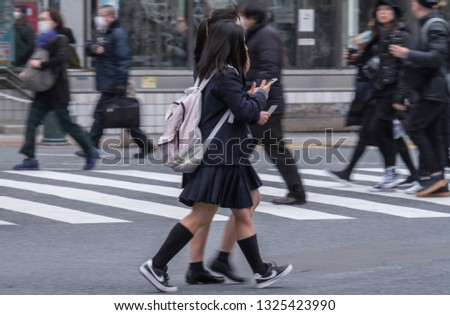 TOKYO, JAPAN - FEBRUARY 27TH, 2019. Japanese school girls crossing the famous Shibuya scramble crosswalk in winter. #1325423990