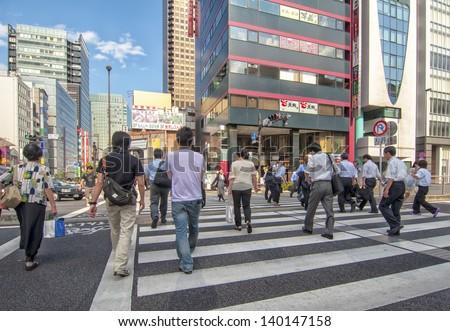 TOKYO,JAPAN-JULY 5: Unidentified people crossing in zebra crossing located in Hamamatsucho,Minato,Tokyo on July 5,2011 in Tokyo,Japan