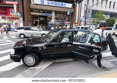 TOKYO, JAPAN-JULY 5: unidentified person out of a taxi in Shinjuku district on July 5, 2011 in Tokyo,Japan.Tokyo has around 35,000 taxi drivers and divided into 33 different companies.