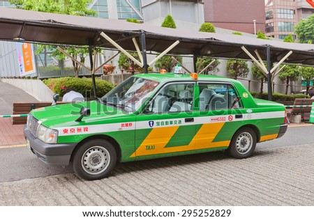 TOKYO, JAPAN - MAY 25, 2015: Green taxi car waiting client near Tokyo Tower in Tokyo, Japan. Green taxies are operated by Tokyo Musen Taxi Cooperation