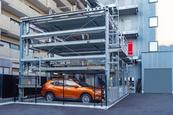 Tokyo. Japan. Multi-storey car parking. Modern parking in Tokyo. Street parking in Japan. Place to store cars. Saving urban space. Robotization. Japan urban. Car stands in an automatic car-park.