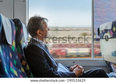TOKYO, JAPAN - NOVEMBER 23: Japanese commuter in Tokyo, Japan on November 23, 2013. Unidentified Japanese business man rides a Hikari Shinkansen to travel in bound to Tokyo