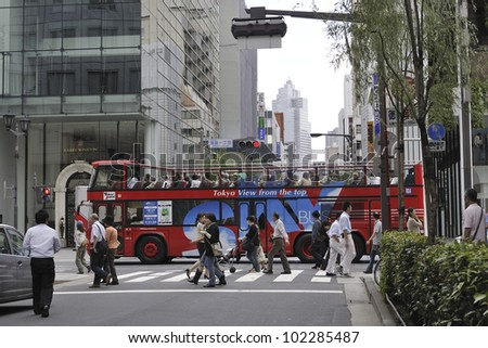 TOKYO, JAPAN - SEPTEMBER 27: Red cruise bus in famous Ginza district on Sept. 27, 2008 in Tokyo, Japan. Cruise bus is popular tourists attraction to enjoy the Tokyo  sightseeing in short trip. - stock photo