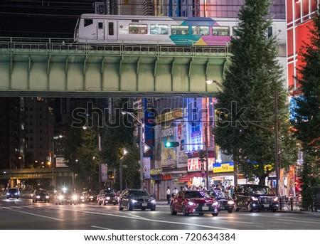 TOKYO, JAPAN - SEPTEMBER 21ST, 2017. Traffic at Akihabara street at night with Japan Railway train passing over on an overhead bridge.