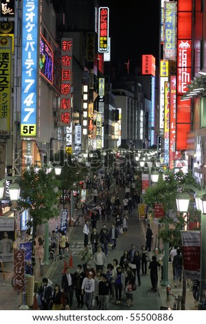 TOKYO - JUNE 13: People walk through light up streets with neon signs on June 13, 2010 in Tokyo.