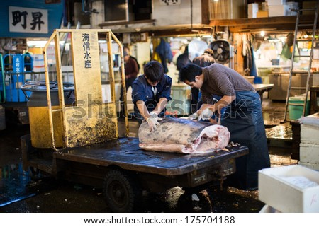 TOKYO - 1 NOV : Tsukiji market, the world biggest fish market in the world. Fish merchant cut the piece of Maguro, Tuna for on the truck. On NOVEMBER 1, 2013 in Tokyo, Japan
