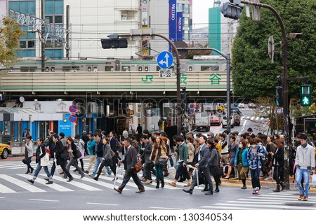 TOKYO - NOVEMBER 12: People crossing the street at Shibuya crossing in Tokyo on November 12, 2012. This location is one of busiest in Tokyo and recognized thanks to being featured in multiple films.