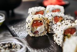 Tokyo salmon uramaki sushi with rice, cream cheese, tomatoes, cucumber, sesame and nori close up. Macro shot of japanese food uramaki rolls with smoked fish and fresh vegetables