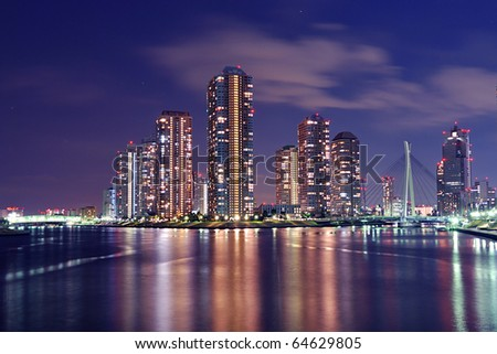 Tokyo skyline by night in modern Tsukishima district with scenic water reflection in Sumida river waters
