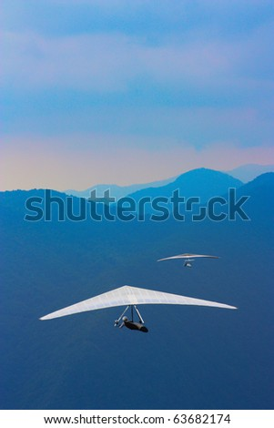 TOLMIN, SLOVENIA - AUGUST 20: Unidentified competitors sore over Kobala mountain during the Kobala Open-2010 hang gliding competitions on August 20, 2010 near Tolmin, Slovenia.