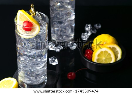 Tom Collins Cocktail or John Collins Cocktail with lemon and maraschino cherry in collins glasses, copy space. Photo stock ©