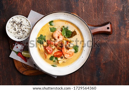 Tom kha kai or tom kha gai, traditional Thai coconut soup with shrimps, mushrooms and chicken served with boiled rice on dark wooden plywood background. Overhead view Foto stock ©