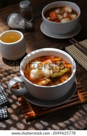 Tom yam soup in a bowl on a wooden table.  Tom yum or tom yam is a type of hot and sour Thai soup, usually cooked with shrimp.  The words of Tom refers to the boiling process, while Yam means mixed Foto stock ©