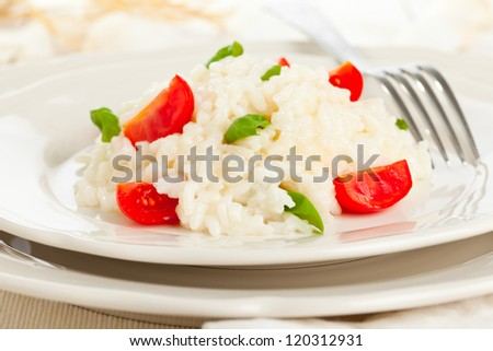 Tomato and basil risotto on white plate on table