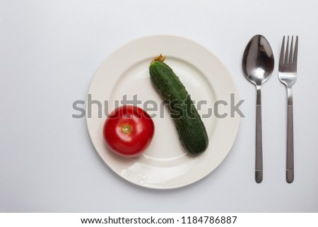tomato and cucumber on a plate in the middle, cutlery on white background. concept of diet, healthy food, small portions, natural.