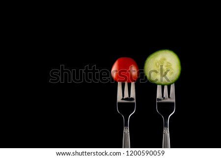 Tomato and cucumber on fork on black background copy space
