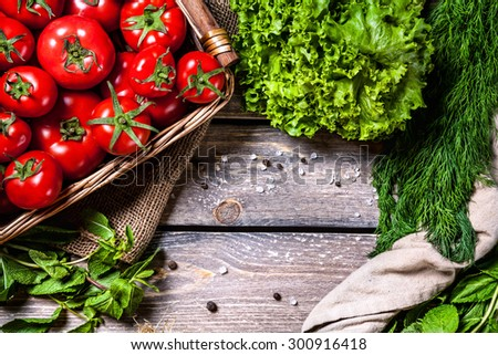 Tomato and green vegetables on the wooden table in the kitchen
