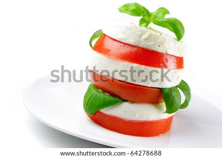 tomato and mozzarella slices decorated with basil leaves on a plate and white background