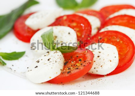 Tomato and mozzarella with basil leaves on a plate