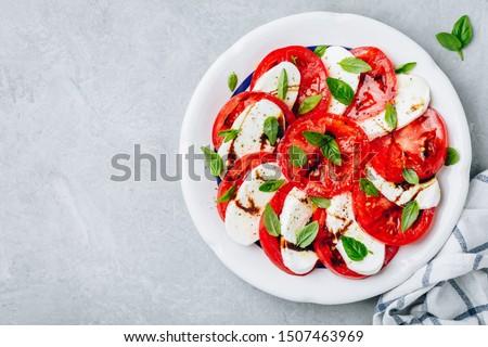 Tomato, basil, mozzarella Caprese salad with balsamic vinegar and olive oil. Top view, gray stone background Stok fotoğraf ©