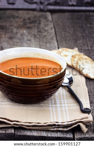 Tomato Bisque with crackers over a rustic background.