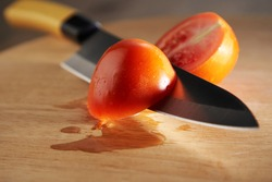 tomato cut to half with knife on the cutting board