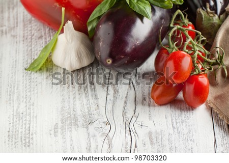 Tomato, garlic, basil and eggplant on white wooden table